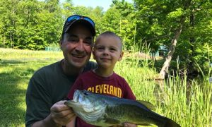 Man and Young Boy Holding Fish